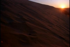 The golden hour sun hangs over large sand dunes in a desert. Stock Footage