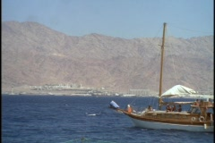 A sail boat sails near the desert. Stock Footage