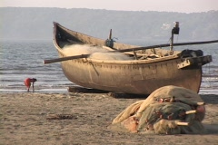 A woman stands near a beached fishing boat. Stock Footage