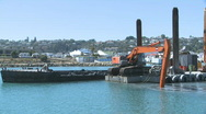 Dredge at work deepening a harbor entrance Stock Footage