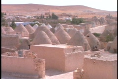 Domed mud houses sit in a village in the desert. - stock footage