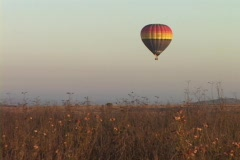 A hot air balloon hovers over fields. Stock Footage