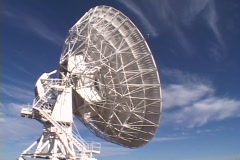 A satellite dish sits before a brilliant blue sky in New Mexico. - stock footage