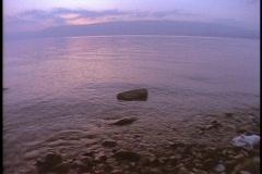 A gentle tide rolls over rocks in the Sea of Galilee. Stock Footage