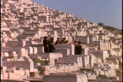 Orthodox Jews stand in a cemetery at the Mount of Olives, Jerusalem. Stock Footage