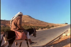 An Arab man rides a donkey down a lonely road. Stock Footage