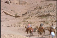 People ride on camels to ruins in Petra, Jordan. Stock Footage
