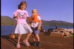 Children perform a silly dance on a dock. Stock Footage
