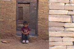 An American Navajo boy sits in a doorway of a pueblo in Chaco Canyon, Arizona. Stock Footage
