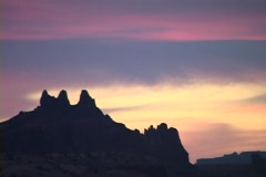 The colorful sky silhouettes rock formations in the Utah desert. Stock Footage