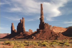 The Totem Pole stands against a blue sky in Monument Valley, Utah. Stock Footage