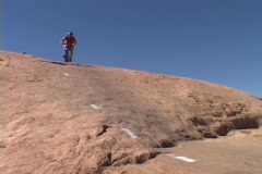A mountain biker rides down a rocky hill in Moab. Stock Footage