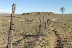A barbed wire fence stretches across a prairie towards a windmill and a desert Stock Footage