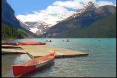 Canoes float beside a dock in scenic Lake Louise. Stock Footage