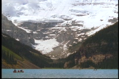 Boaters float in Lake Louise past the Canadian Rockies. - stock footage