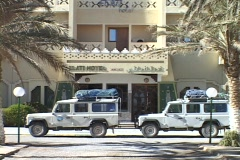 Land Rovers sit parked in front of a hotel prepared for a safari. Stock Footage