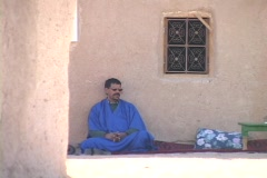 A man in a blue robe sits against a stone wall. Stock Footage