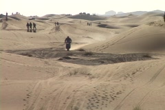 A motorcyclist rides across sand dunes. Stock Footage