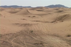 A rally car speeds through sand dunes as spectators watch. Stock Footage