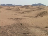 A rally car speeds through sand dunes as spectators watch. Stock Footage