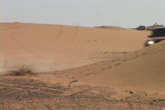 A rally car speeds around a sand dune and out of sight. Stock Footage
