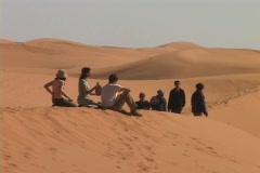 Spectators sit and drink while others walk along sand dunes as they wait for Stock Footage