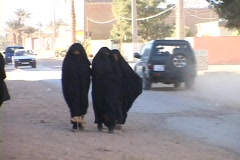 Women walk along a busy street dressed in burqas. - stock footage