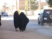Women walk along a busy street dressed in burqas. Stock Footage