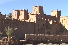 A stone wall surrounds a city in the Morocco desert. - stock footage