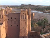 A building with decorative towers resides in a Morocco desert valley. Stock Footage