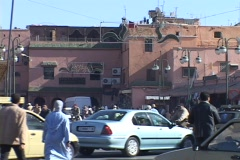 Pedestrians and cars move along congested city streets in Marrakesh Morocco. Stock Footage