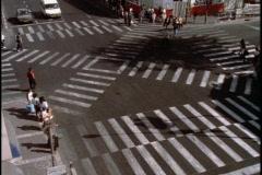 Stock Video Footage of Pedestrians cross an intersection on crosswalks.