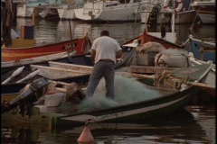 A fisherman works on his net on a small boat in a harbor. Stock Footage