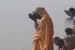 An Indian woman prays next to the Ganges as men nearby bathe in the river. Stock Footage