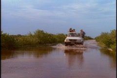 Tourists ride in the back of a jeep through a flooded area. Stock Footage