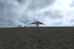 A hang-glider runs and flies out of sight after a successful take-off. Stock Footage