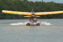 An ultralight airplane skids across the water and begins to take-off into the Stock Footage