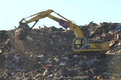 A large scoop shovel dumps debris from Hurricane Katrina. Stock Footage