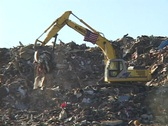 Stock Video Footage of A large scoop shovel dumps debris from Hurricane Katrina.
