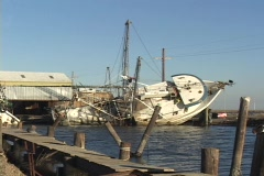 A damaged fishing boat rests on its side after Hurricane Katrina. Stock Footage
