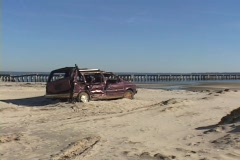 A destroyed minivan abandoned on a beach shows the destruction caused by Stock Footage