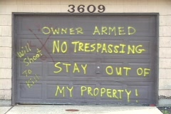 A home owner puts a message on their garage door warning trespassers to stay Stock Footage