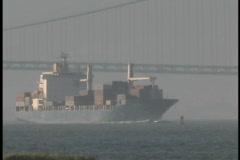 A cargo ship passes under the Manhattan Bridge. - stock footage