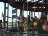A medium shot of a merry-go-round in motion. Stock Footage