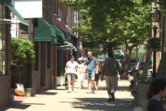 A medium shot of people strolling down the sidewalk in a quaint city. Stock Footage