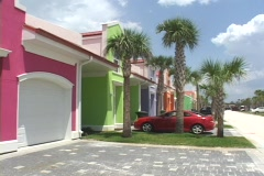 A car sits in a driveway in front of a green beach house. Stock Footage