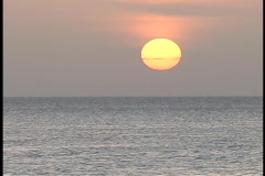 The sun hovers over calm water during golden hour. Stock Footage