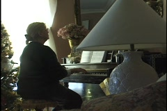 A woman plays a piano in a living room. Stock Footage