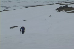 Following-shot of a cross country skier striding up a snowy hillside. - stock footage
