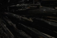 Pan-up shot of racks of weapons in a munitions depot. Stock Footage